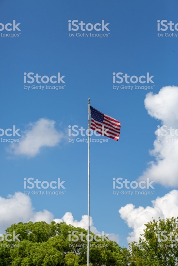 The American Flag with puffy white clouds and blue sky